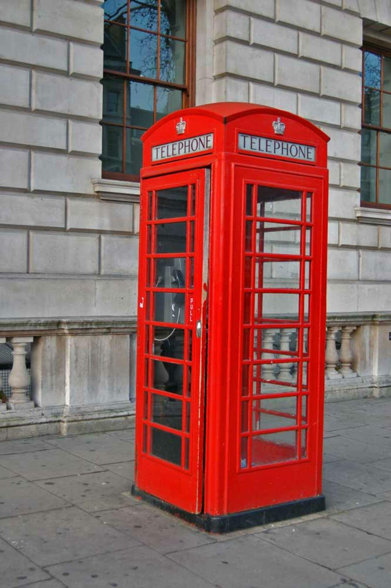 Английский красный таксофон и девушка на таксофоне фото